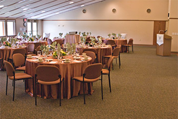 Photo of a large room set with tables for special UW event.