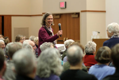 Karen Oberhauser passes the microphone for audience questions during her Winter Enrichment lecture
