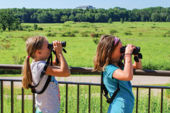 Young girls looking through binoculars