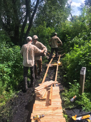 Student rangers installing new boardwalk at Ho-Nee-Um Pond