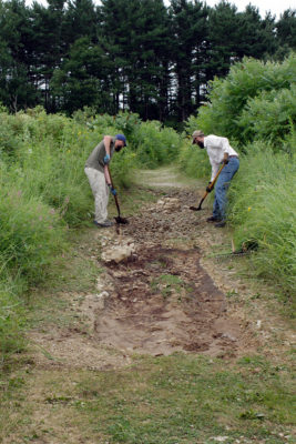 Land care staff repairing a washed out trail in Curtis Prairie.