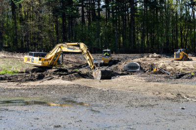 An excavator dredges Curtis Pond